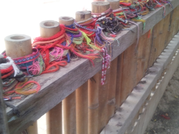 People leave bracelets at burial markers in the Killing Fields